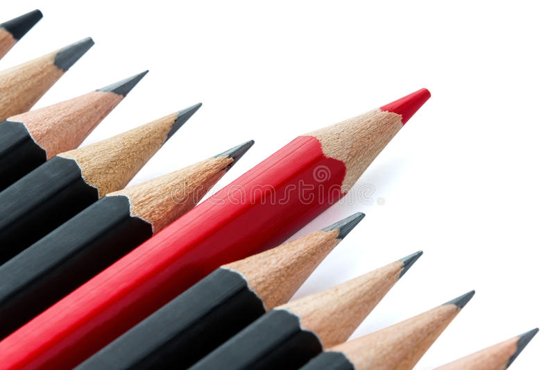 Row of black pencils with one red pencil. One red pencil standing out from the row of black pencils royalty free stock images