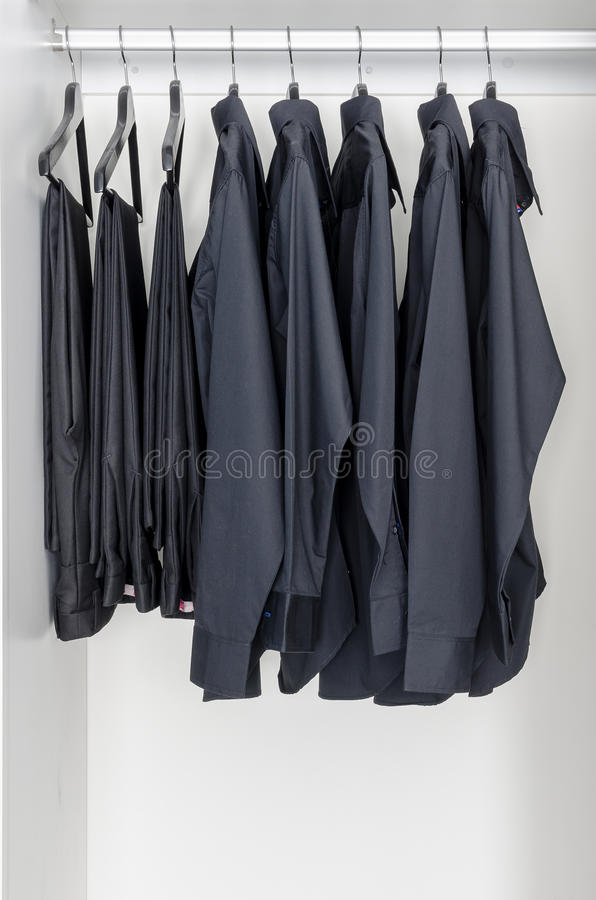 Row Of Black Shirts And Pants Hanging On Coat Hanger Stock