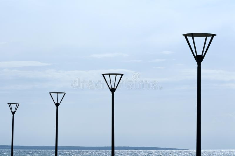 Row of street lamps at seafront. Row of the black street lamps at the seafront in front of the pale gray sky and the glittering blue sea stock photography