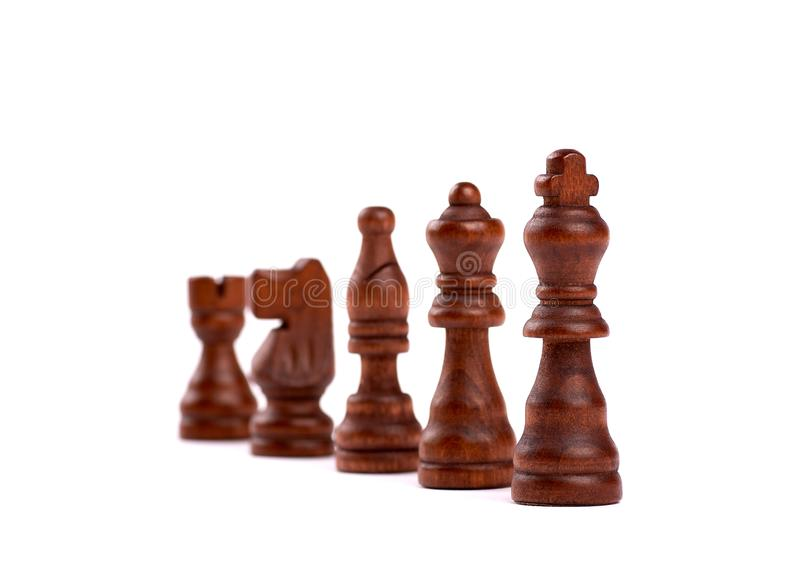 Row of black wooden chess pieces. Team Hierarchy With Defocused Background. Isolated On White Background. Row of black wooden chess pieces. Team Hierarchy With royalty free stock photos