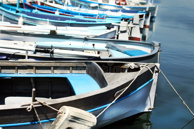 Row of blue fishing boats resting on blue water on sunny day. Row of blue fishing boats resting on blue water, marina, transportation, mediterranean, background stock photos