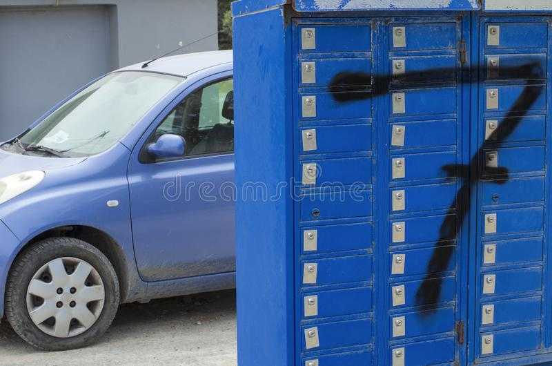 Row of blue mailboxes closed on locks with a large black number Seven. And in the background a fragment of a blue car Rhodes, Greece stock image