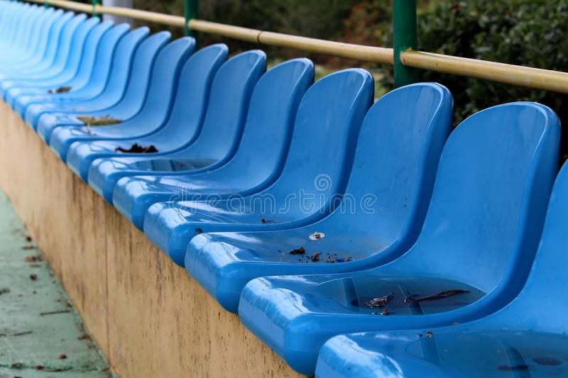 Row of blue plastic seats mounted on top of concrete bleachers with metal fence and trees in background next to basketball court royalty free stock images