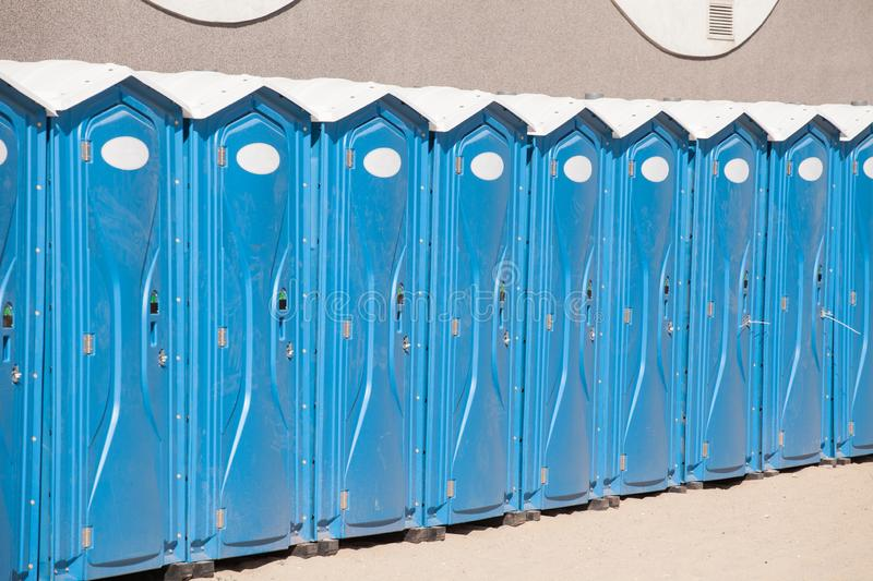 Row of blue portable, mobile toilets stock photography