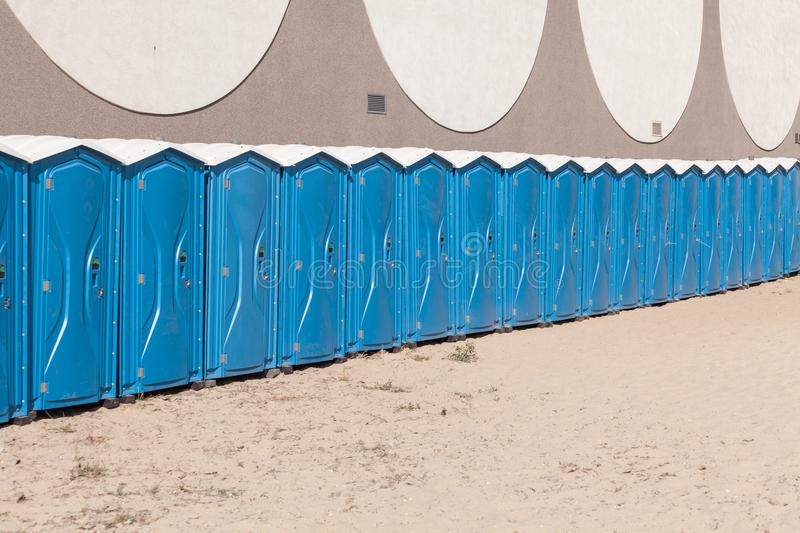 Row of blue portable, mobile toilets stock photo