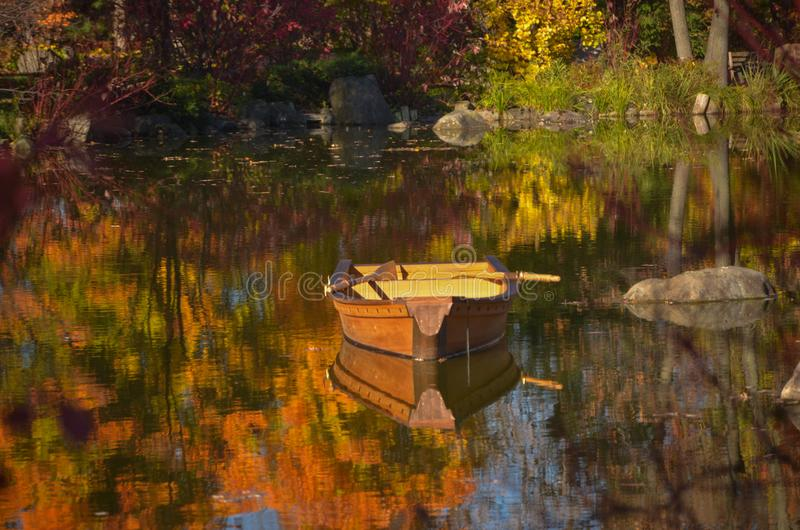 The Row Boat. A row boat afloat on a pond with fall color reflecting around it on a calm pond royalty free stock image