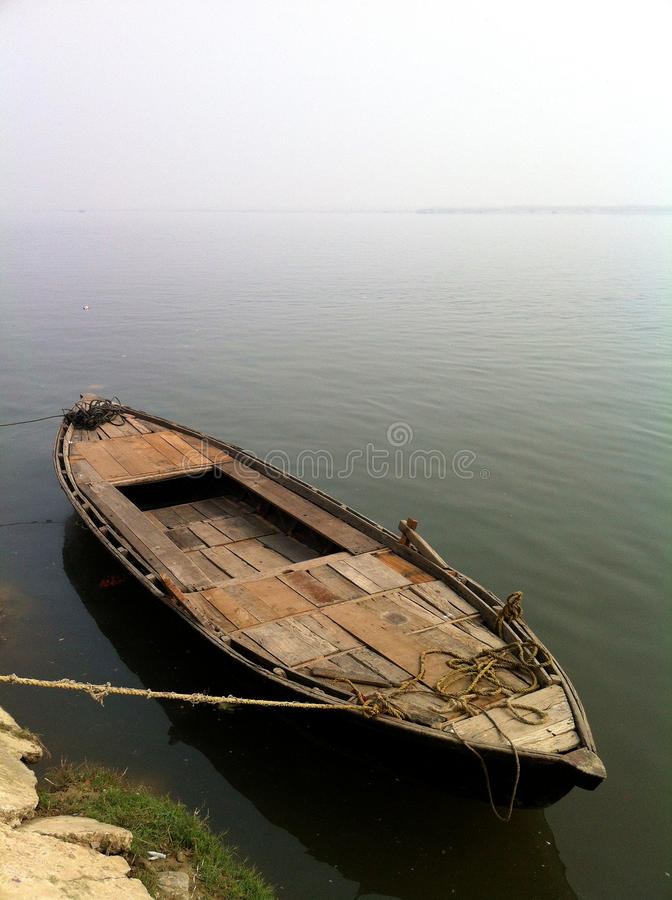 Row Boat Varanasi Side View. A stunning image of a hand built wooden row boat tied up on the shores of the Ganges river in Varanasi stock photography