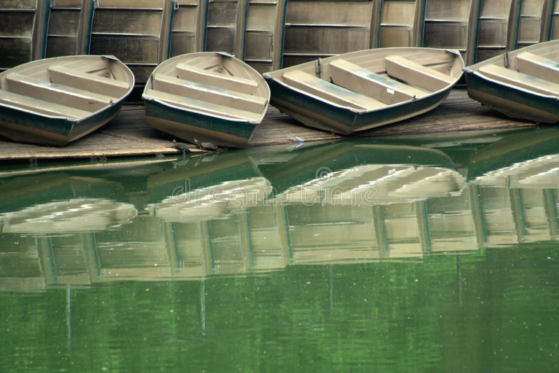 Row Boats. A shot in Central Park in New York City of some old tarnishing row boats and a bunch of row boats lined up on their side, resting on the shore and royalty free stock image