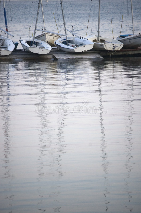 A row of boats. At jetty in evening time with mast reflection on the water. Vertical composition stock photography