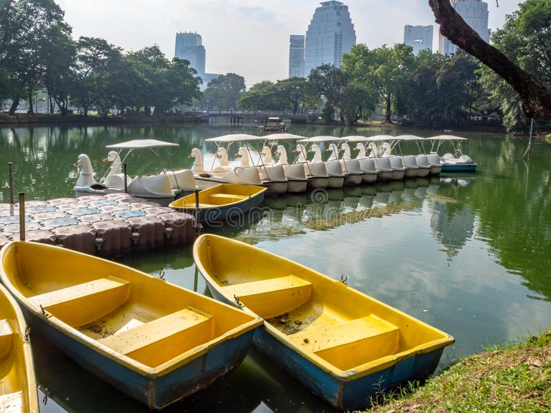Row boats and pedal boats in pond with cityscape background. Row boats and pedal boats are parked in the pier in the city center park with cityscape background stock photography