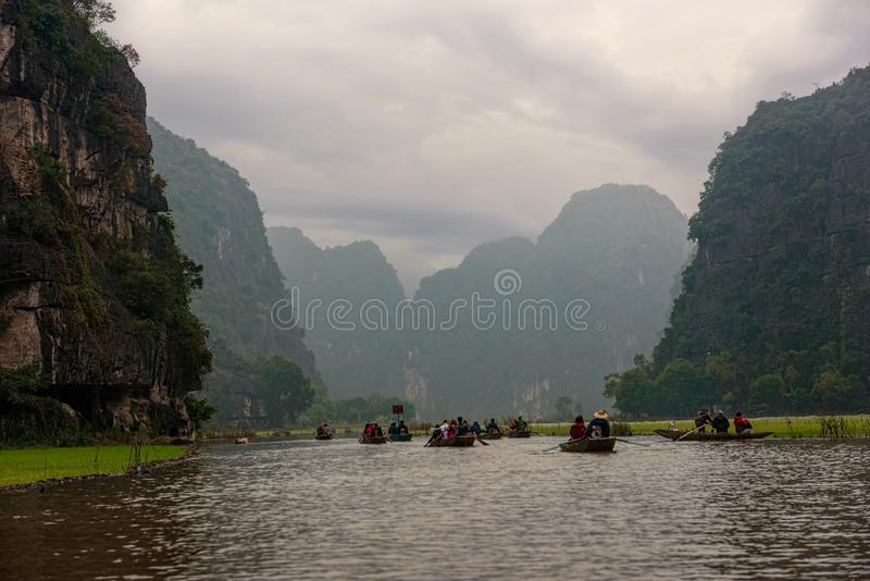 Row boats on a river under cast sky in Vietnam. Between rice fields royalty free stock images