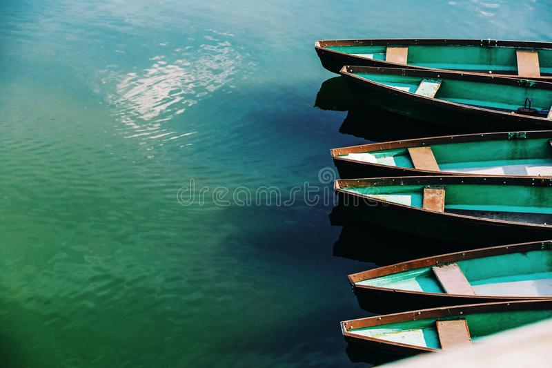 Row boats in a water. Green row boats arranged in a turquoise water, copy space stock photography