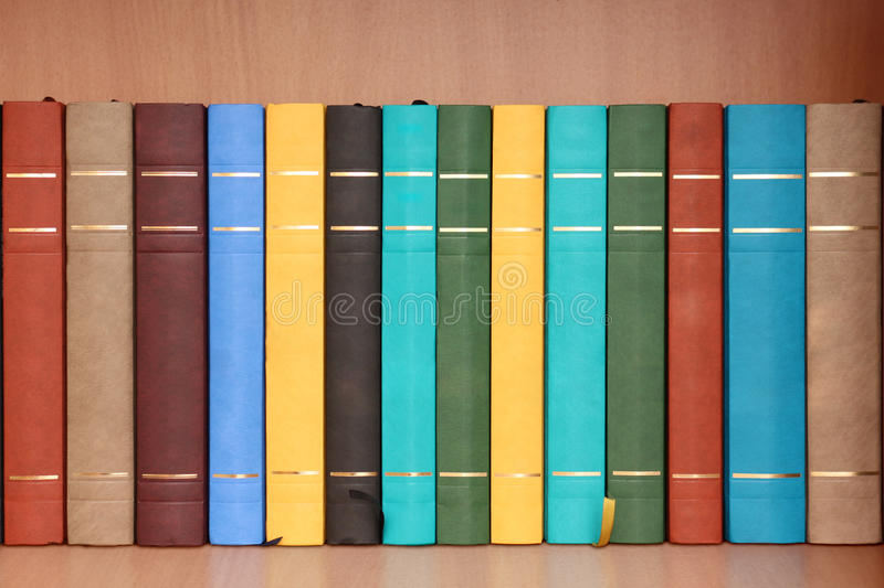 Row of books in wooden cabinet. A row consisting of 14 books of different colors in a wooden cabinet stock photo