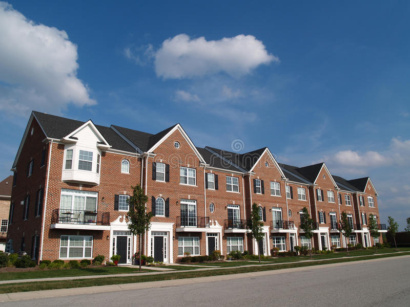 Row of Brick Condos With Bay Windows. A row of brick condos or townhouses with bay windows beside a street royalty free stock image