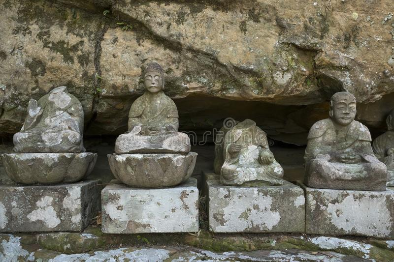 Row of broken old stone Buddha statues in Meganeiwa park, Sasebo royalty free stock image