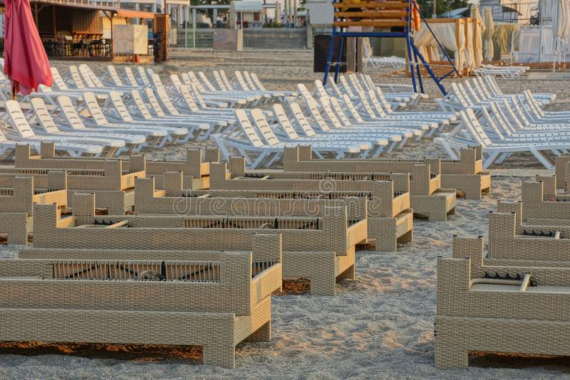 A row of brown and white sun beds on the sand of the sea beach. A row of empty brown and white sunbed on the sand of a sea beach royalty free stock photos