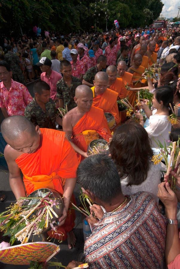 Row of Buddhist Monks on Tak Bat Dok Mai-Merit Flower Festival in Thailand. stock photos