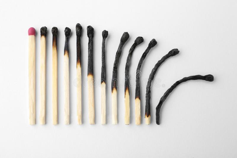 Row of burnt matches and whole one on white background. Human life phases concept. Row of burnt matches and whole one on white background, top view. Human life stock photo