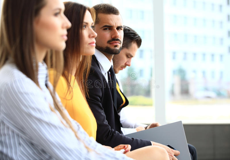 Row of business people making notes at seminar royalty free stock image