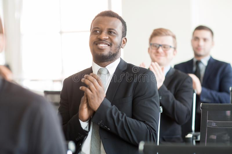 After presentation. Row of businessmen clapping hands while congratulating speaker on success after presentation royalty free stock photos