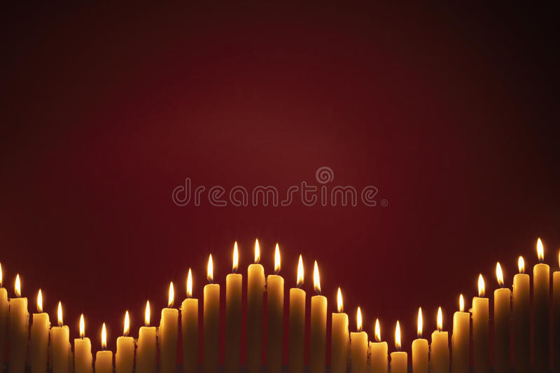 Row of Candles. Row of different sized burning Candles with abstract background stock image