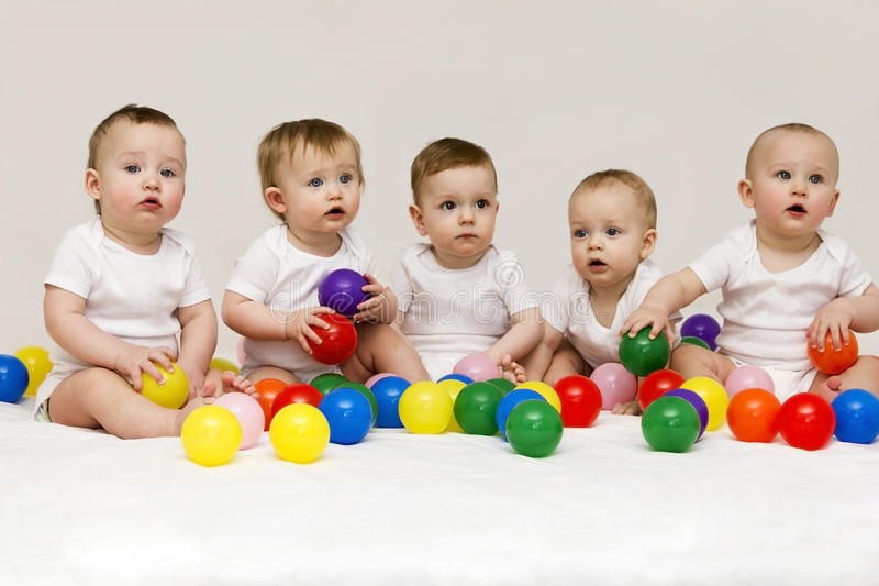 Row of caucasian babies sitting side by side looking away isolated on gray background. Five cute babies playing with royalty free stock photo