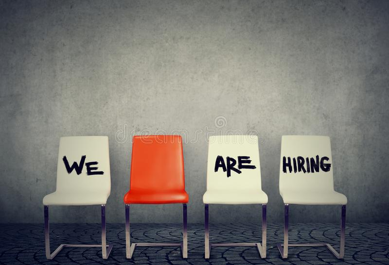 Vacant places for new employees. Row of chairs saying We are hiring offering vacant places royalty free stock images