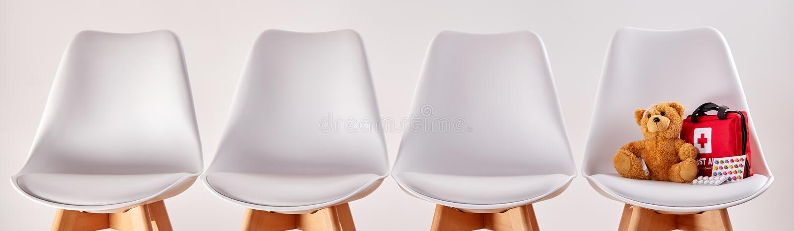 Row of chairs with teddy bear and first aid kit stock images