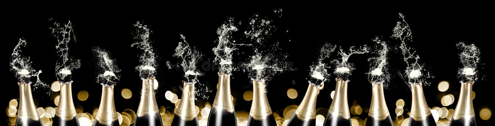 Foaming and splashing champagne bottles banner royalty free stock photo