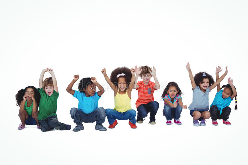 A row of children crouching down together. Against a white background stock photo