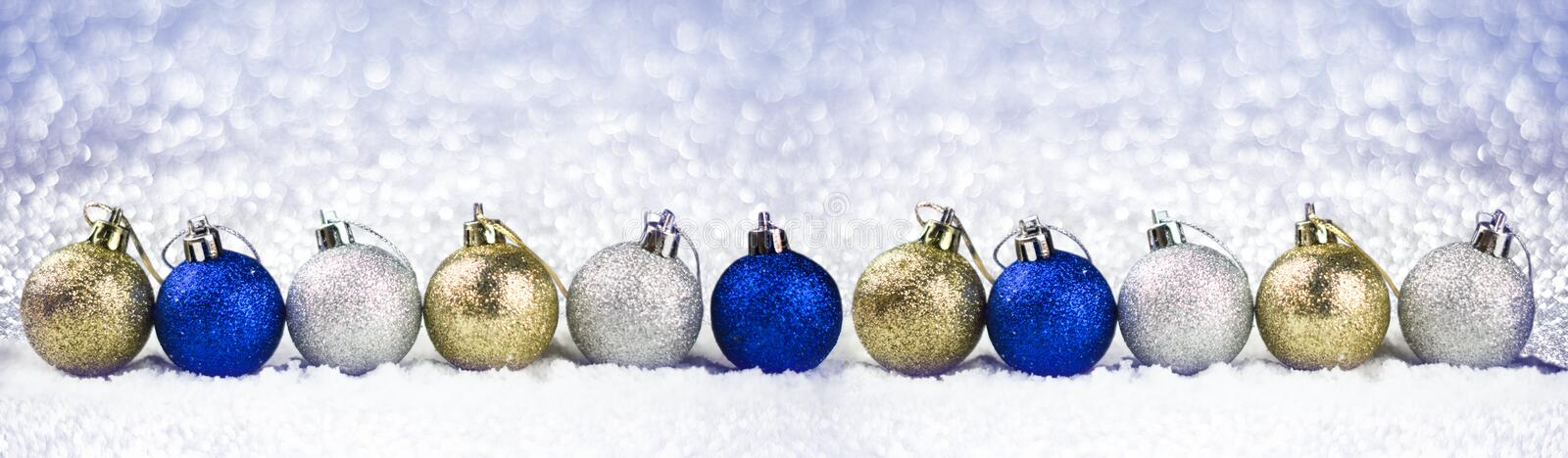 Row of christmas balls in the snow on the background sparkles stock photos