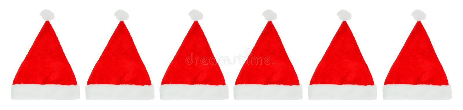 Row of Christmas Santa hats. Several red and white Christmas Santa hats in a long row royalty free stock images