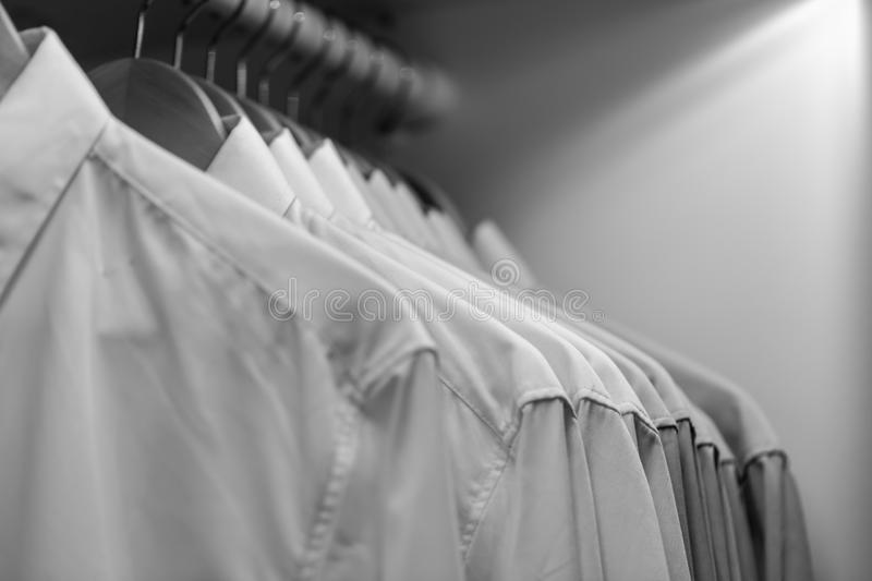 Row of clean new orderly cloth in wardrobe urban people lifestyle. Concept in black and white color tone royalty free stock image