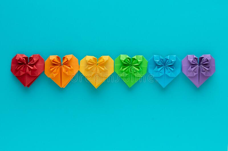 Coloured hearts in a row on a blue background. LGTB+ concept. Valentine`s Day. Copy space stock image