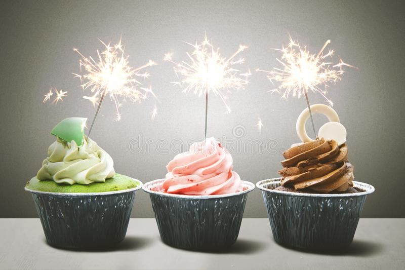 Colorful birthday cupcakes. Row of colorful birthday cupcakes with sparklers above table stock photos