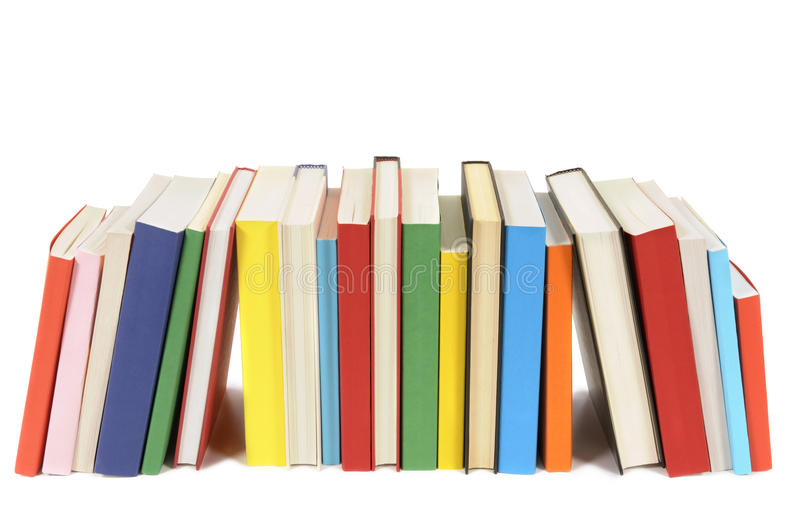 Row or library of books, some leaning, isolated on white background stock image