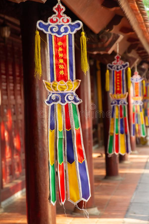 Colorful flags hanging in the courtyard  at the Tran Quoc Pagoda in Hanoi, Vietnam. Row of Colorful flags hanging in the courtyard  at the Tran Quoc Pagoda in stock photo