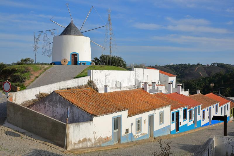 A row of colorful houses along a steep cobbled street inside Odeceixe near Aljezur, with a whitewashed traditional windmill, Cos stock photos