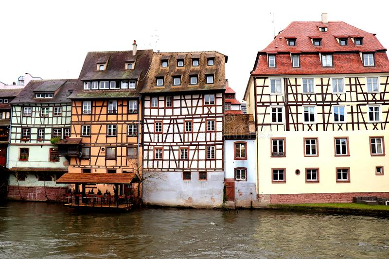 Row of colorful houses in Strasbourg, France. Row of colorful houses and buildings along the water in Strasbourg, France on a cold, rainy day in December during stock photos