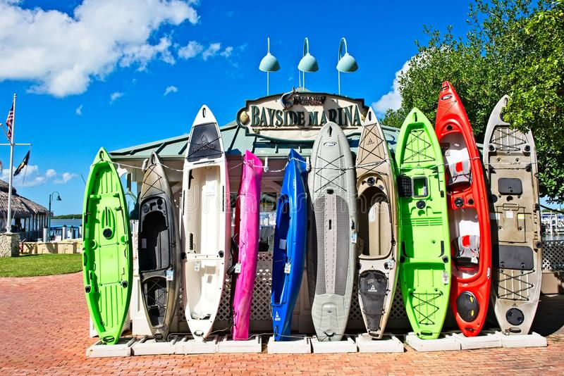 A row of colorful kayaks standing upright against a building at a marina in Islamorada, Florida. A row of colorful kayaks stand against a building at a marina in royalty free stock photography
