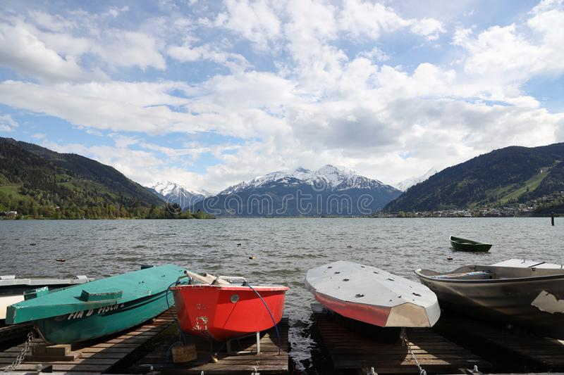 A row of boats at a lake in the Austrian Alps. A row of colorful paddle boats at a lake backed by Alpine mountains with beautiful dramatic clouds stock images