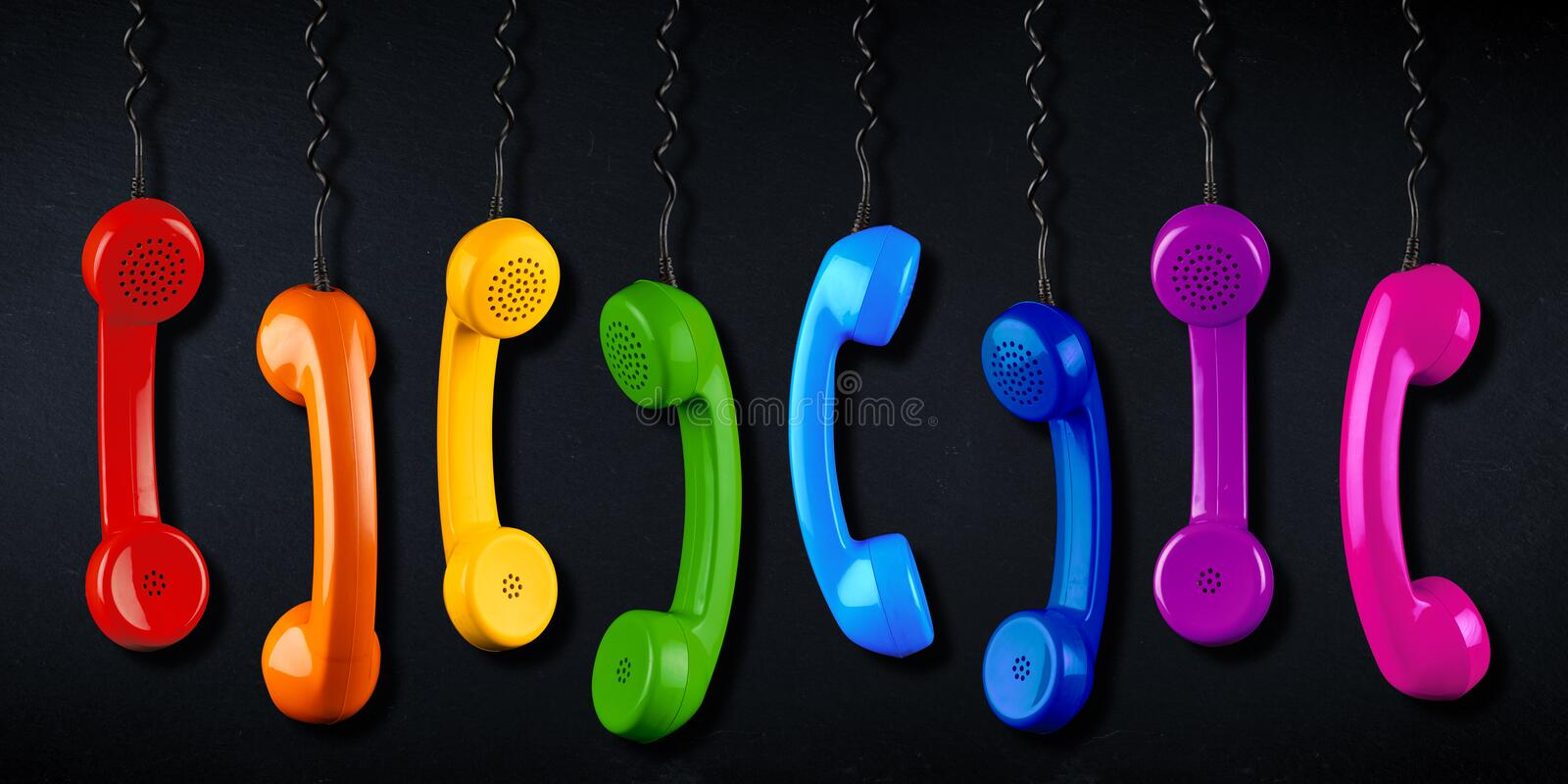 Row of colorful rainbow colored old fashioned retro phone reciever with black telephone wire black slate blackboard background, royalty free stock photos