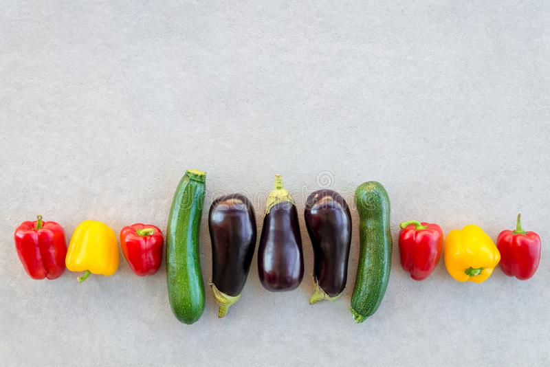 Row of colorful summer vegetables on concrete background. Red and yellow peppers, zucchini and eggplants stock images