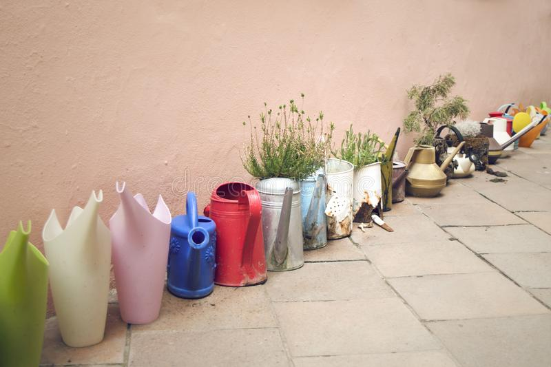 Row of colorful watering cans in alley. Colorful cans for watering and plants put in a row in a small alley in Prague royalty free stock photography