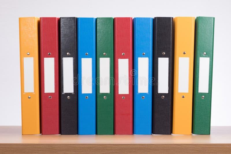 Row of coloured office document folders on shelf stock photography