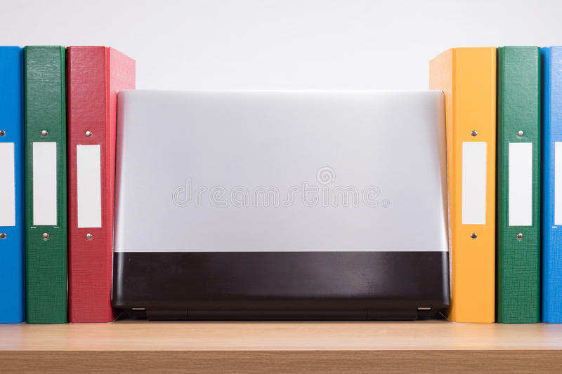 Row of coloured office folders and computer laptop royalty free stock photos