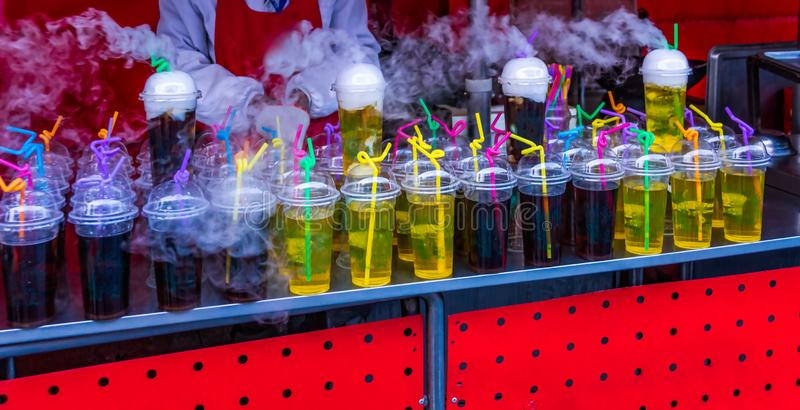 Row of colourful fruit Non-alcoholic drinks in plastic cups with white smoke royalty free stock image