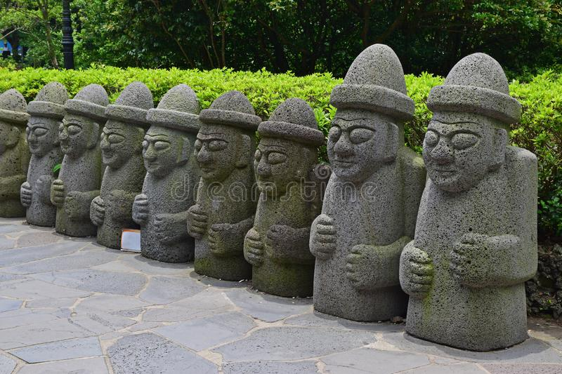 A row of commonly seen Dol hareubangs rock statues in Jeju Island, southern tip of South Korea stock image