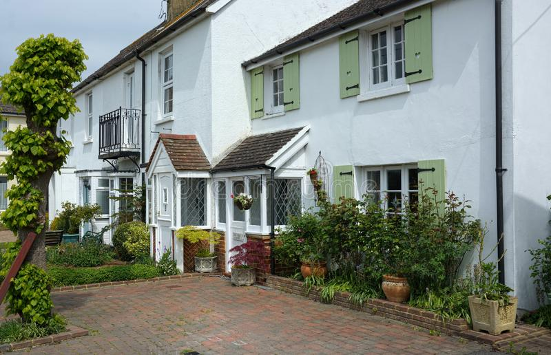 White painted cottages. A row of cottages painted white that give uniformity to two different sized properties stock photography