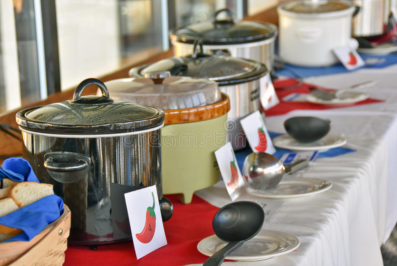 Row of crock pots in chili cook off contest. Row of crock pots with signs and ladles for chili cook off contest stock images